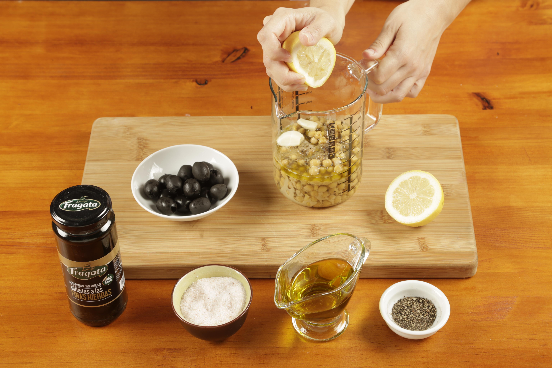 2. Introducir dentro del vaso de la batidora los garbanzos, el ajo, el tahine, el aceite, el comino y el zumo de limón.